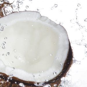Coconut with splashing water over white